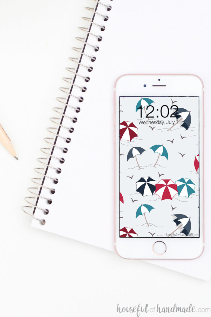 White iPhone with free Digital wallpaper for July on the screen sitting on a notebook.