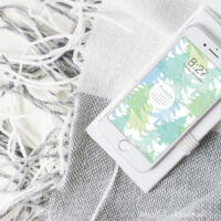 White smartphone with the free digital wallpaper for December, that has a current month's calendar on it, on the screen sitting on a blanket.