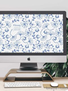 Smartphone with the blue floral digital background on the home screen on a desk next to a notebook.