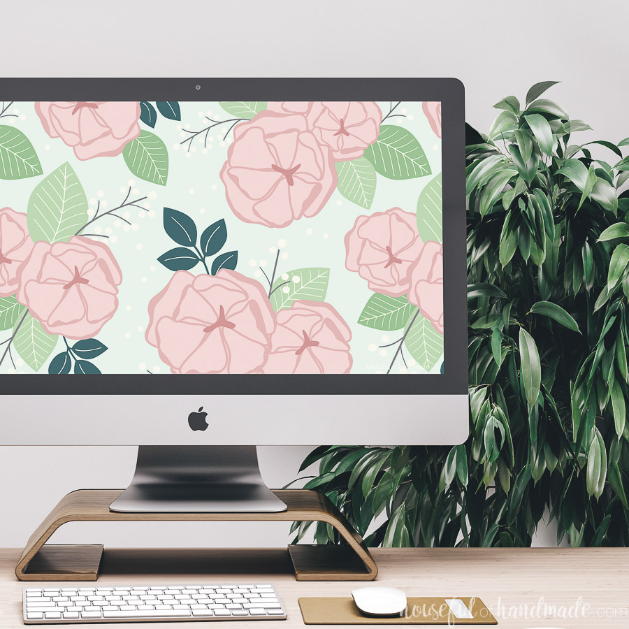 iMac on a desk in front of a plant with a pink and green floral wallpaper on the background.