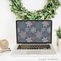 Laptop with the screen up showing the non-traditional snowflake design of the digital backgrounds on the screen.