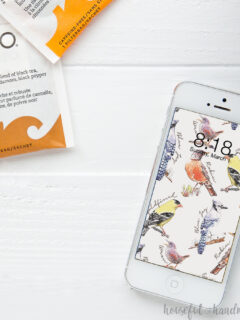 Cell phone with digital backgrounds for March on the screen with spring birds on it.