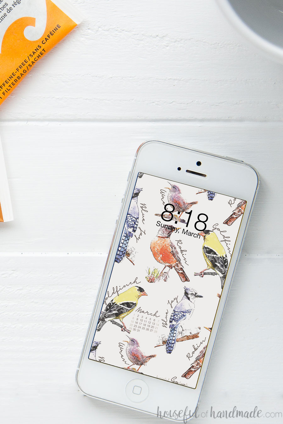 White iPhone with bird sketches wallpaper on the home screen.
