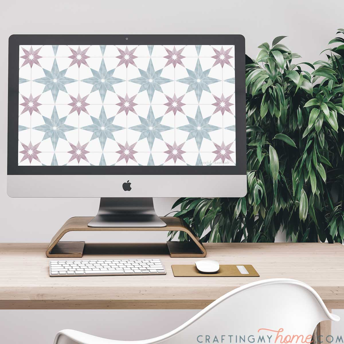 The free digital background for March on the screen of an iMac computer sitting on a desk with a plant behind it.