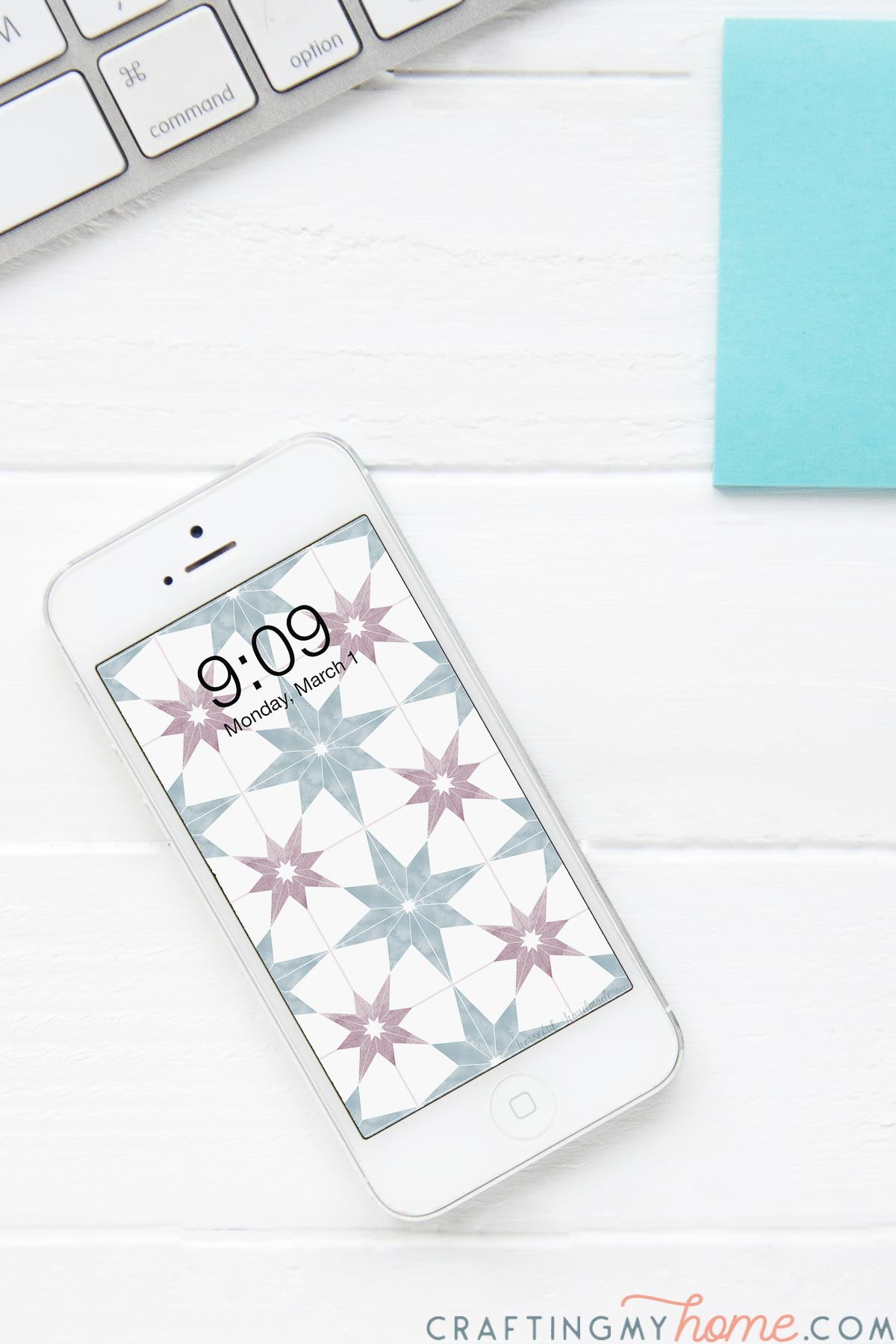 Smartphone on a desk with the patterned tile digital wallpaper on the home screen.