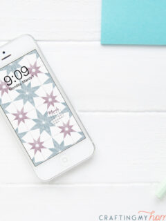 The free digital wallpaper for March with a current months calendar on the screen of a white iPhone sitting on a white desk.