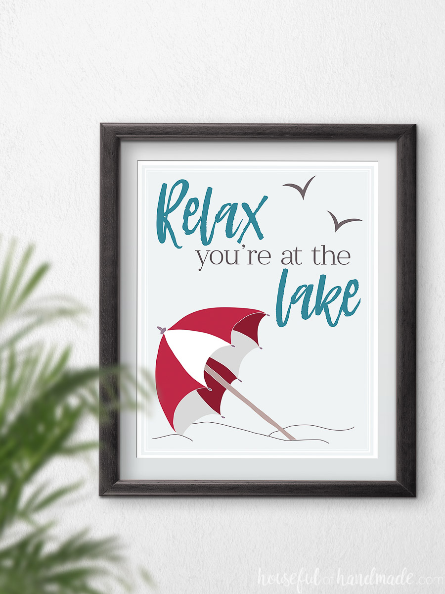 "Red beach umbrella art with text ""relax you're at the lake"" in a frame."