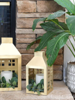 DIY Christmas lanterns painted gold and sitting by the fireplace and a house plant.
