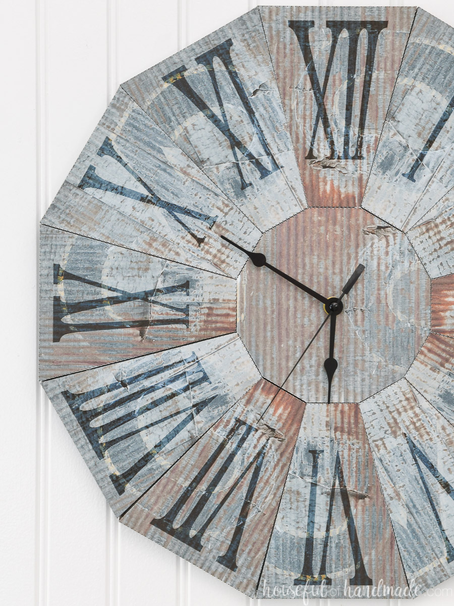 Rusted blue steel clock made out of paper hanging on a beadboard wall.