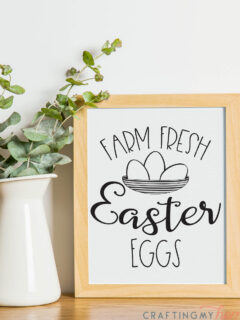 White pitcher with eucalyptus leaves in it next to a natural wood framed beautiful printable Easter sign.
