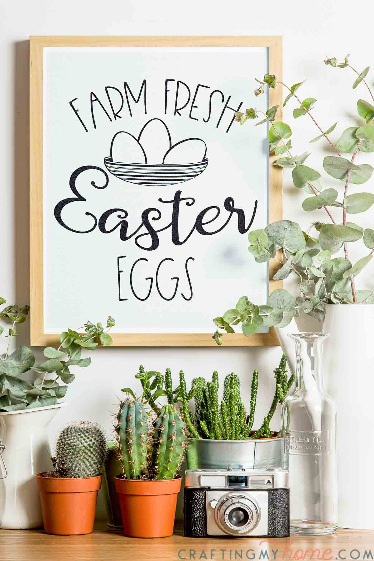 Console with plants on it and frame hanging on the wall above it with the beautiful Easter egg sign in it.