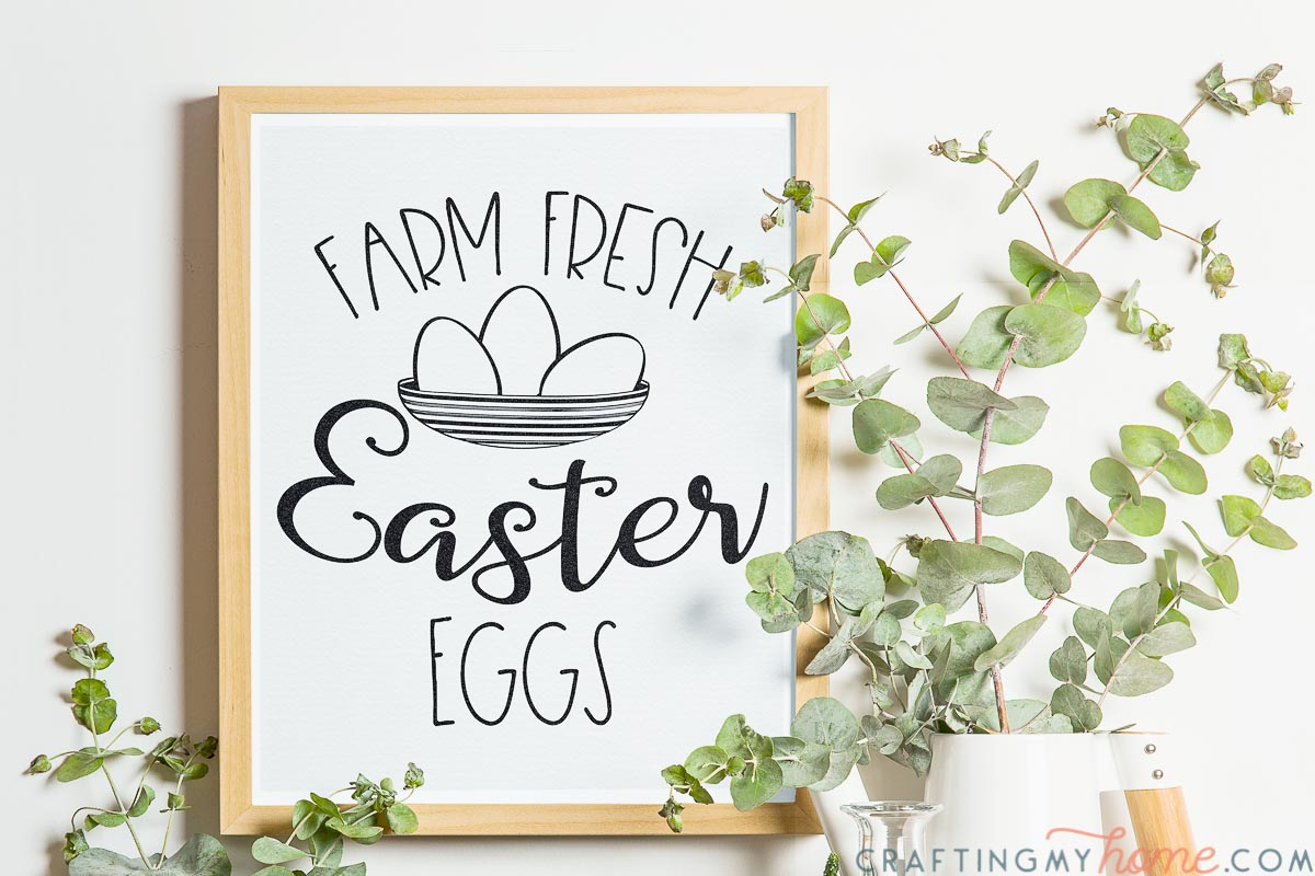 Natural framed photo of the printable Easter sign hanging on the wall with greenery around it.