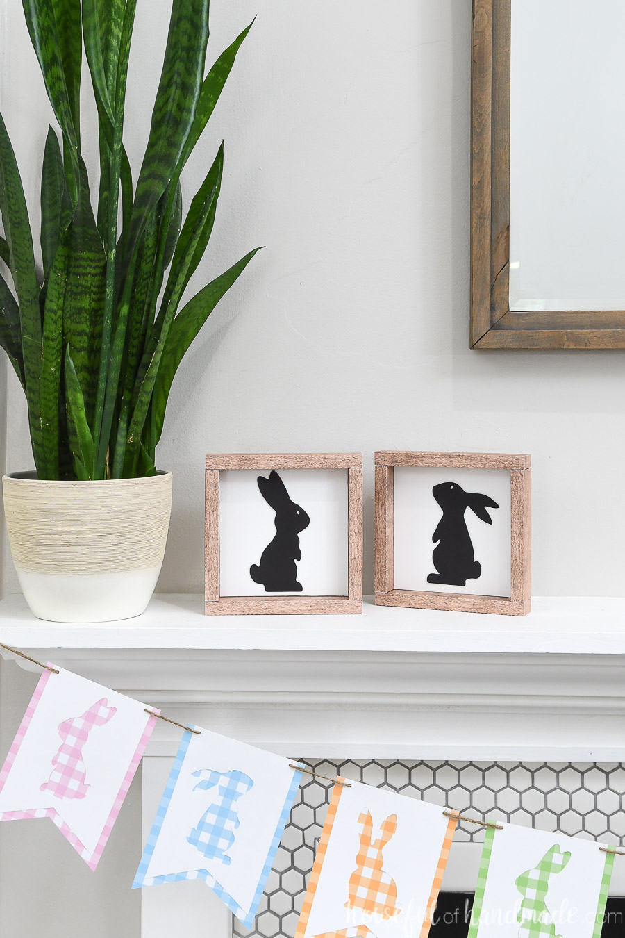 Two bunny silhouette wood signs on a mantel next to a plant.