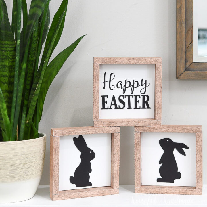 Three simple Easter signs stacked on a mantel next to a snake plant.