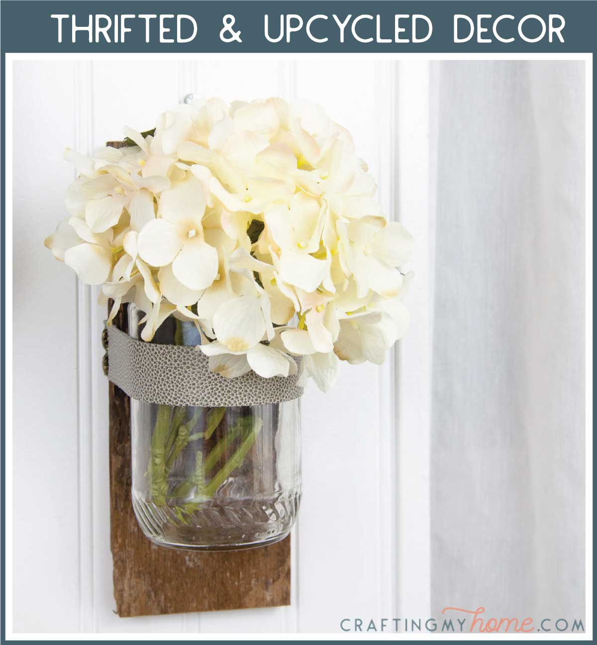 Wall vase made from upcycled items holding flowers with a navy box around it and white text: Thrifted & Upcycled Decor.