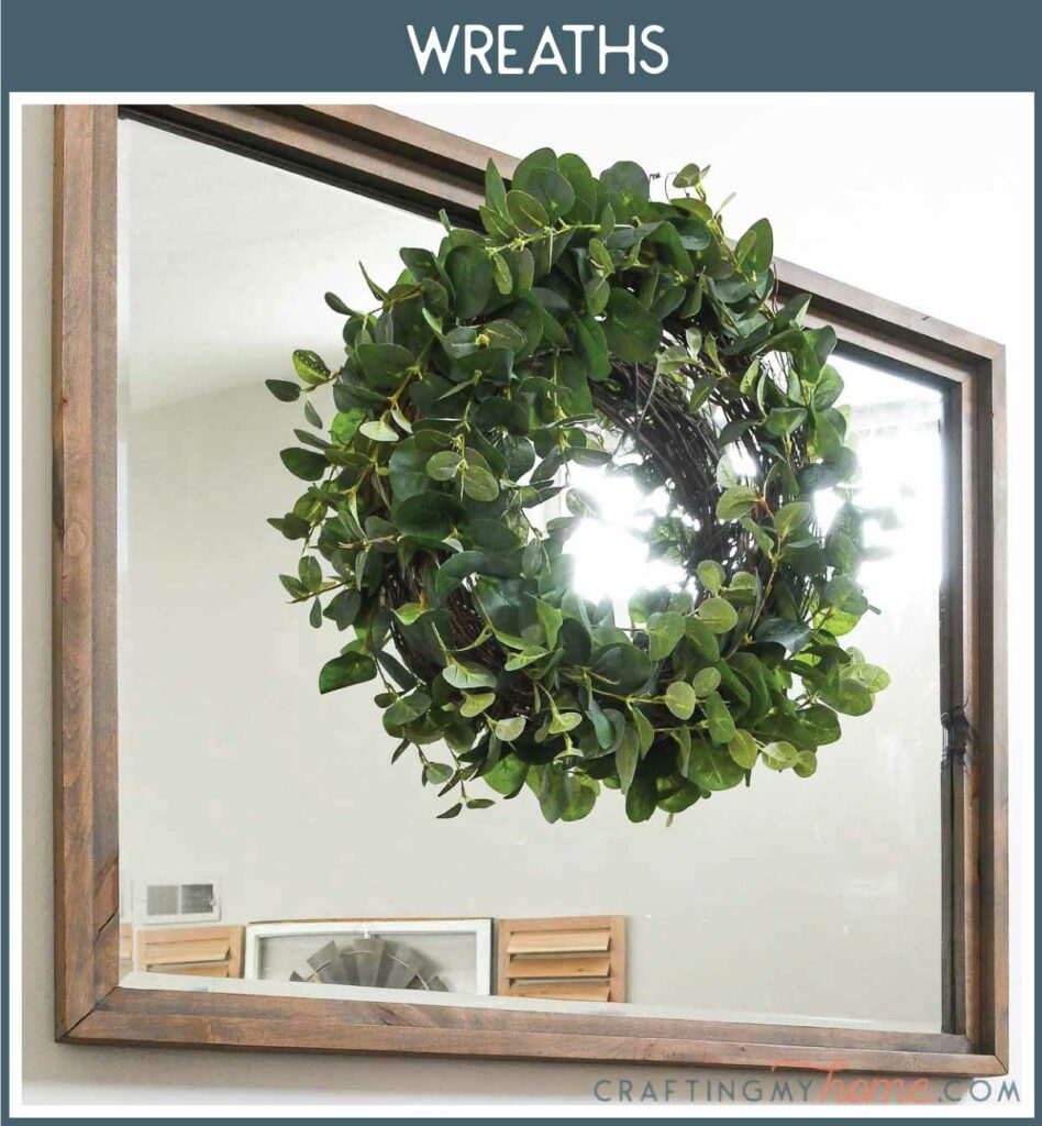 Picture of eucalyptus wreath hanging on a large mirror with a navy box around it and white text: Wreaths.