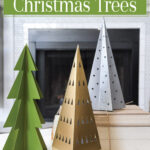 Christmas vignette with 3 paper Christmas trees painted green, gold and silver.