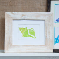 Custom photo mat with printable watercolor seashell in a frame on a mantle