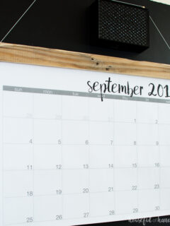 Giant wall calendar attached to a piece of reclaimed wood hanging on a chalkboard wall showing September calendar on the front.