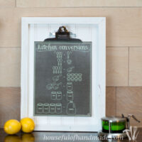 Chalkboard printable kitchen conversion chart on a clipboard with a salt cellar and lemons in front of it.