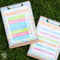 Two printable summer chore charts on clip boards on grass