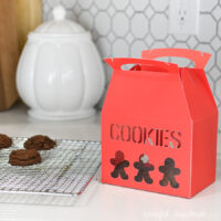 Red Christmas Cookie box with cutout gingerbread cookie shapes for decor.