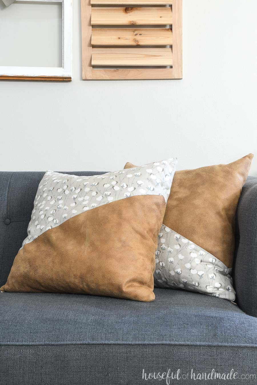Two diagonal cut leather throw pillows on a couch.
