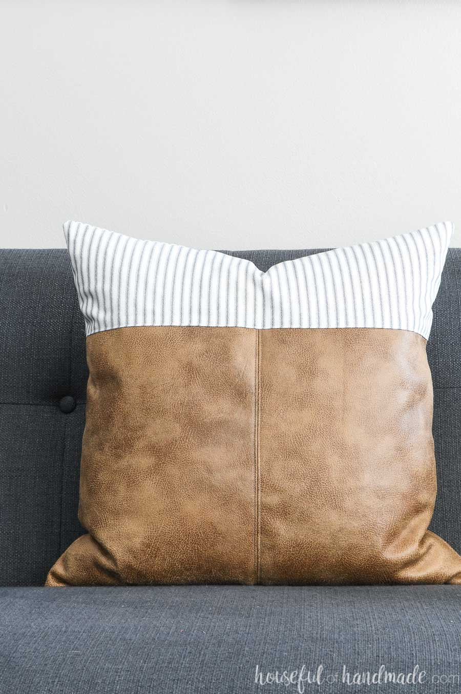 Leather pillow cover with farmhouse ticking fabric and brown leather.