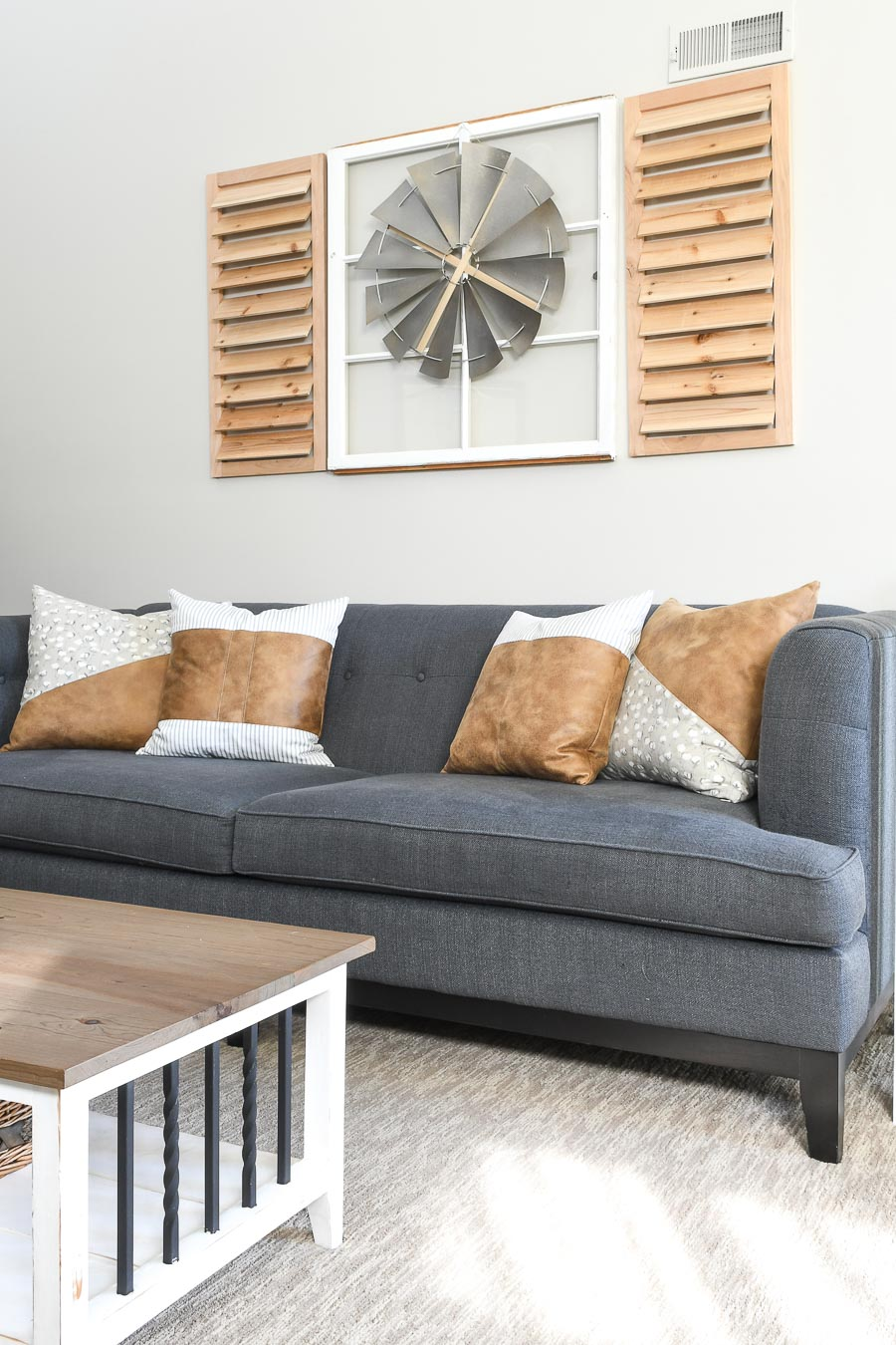 Decorative throw pillows on a couch with windmill decor above it.