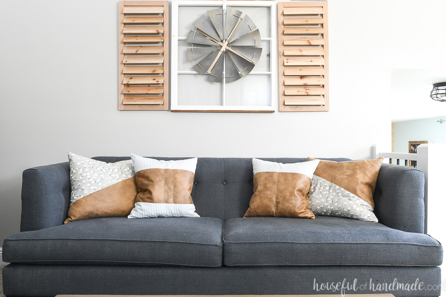 Gray-blue tufted sofa with four decorative leather pillows on it.