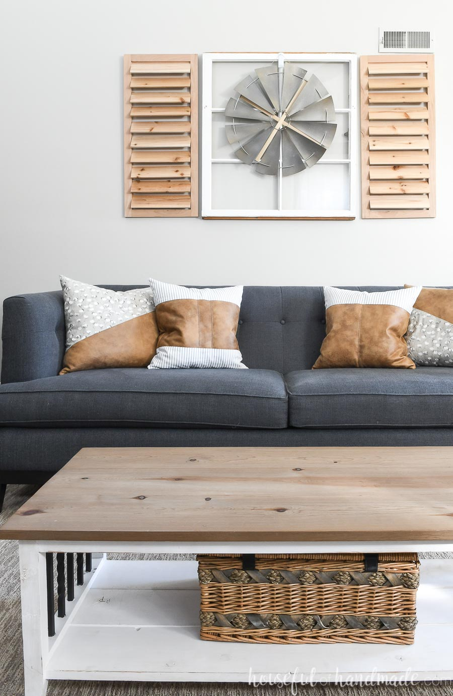 Living room with farmhouse coffee table, navy sofa, and decorative leather throw pillows.