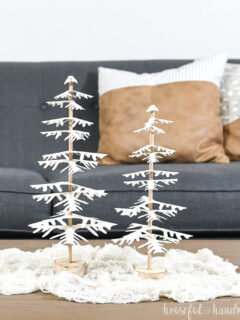 DIY paper Christmas trees made by placing branches on a dowel, sitting on a table.