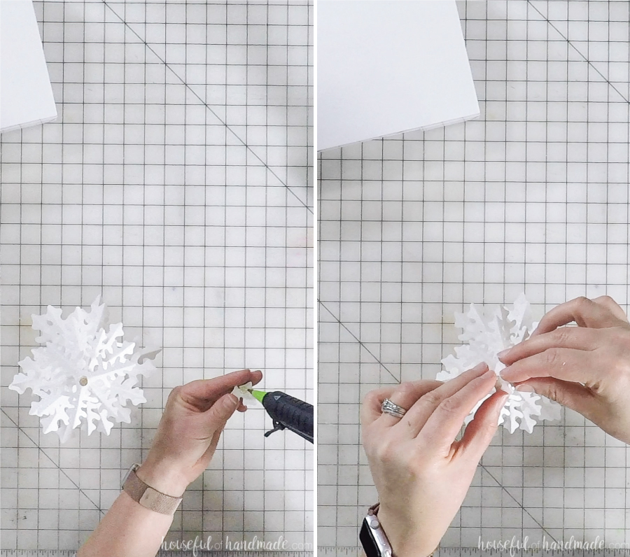 assembling paper christmas trees with hot glue gun to dowel