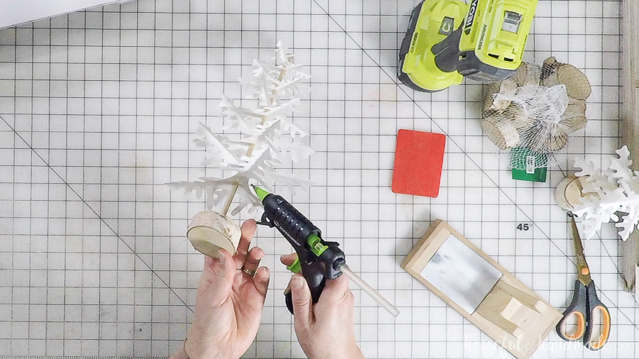 using hot glue gun to secure paper christmas trees to dowel