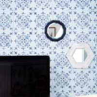 Two wall mirrors, one white hexagon and one blue geometric, hanging on a blue and navy stenciled wall.