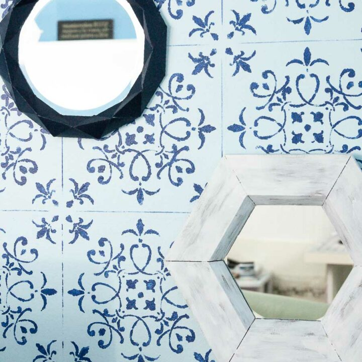 Hexagon wall mirror hanging on a stenciled wall next to another paper wall mirror.