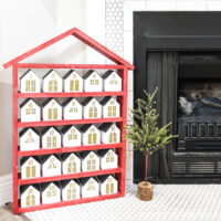 Red house shaped shelf with 25 paper houses as a Christmas advent calendar.