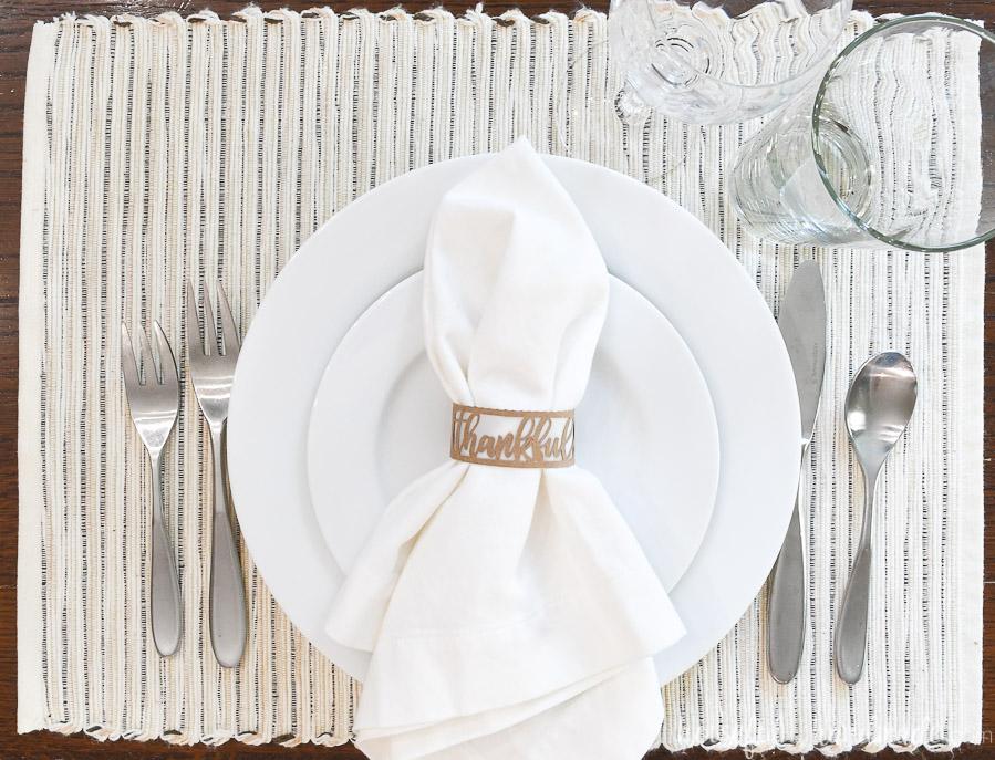 diy thanksgiving napkin rings on white napkin with white plates and silverware