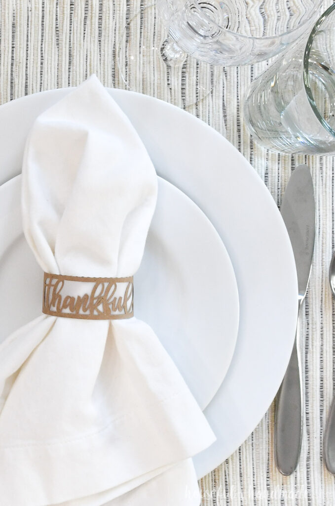 close up of paper thankful napkin ring on white place setting