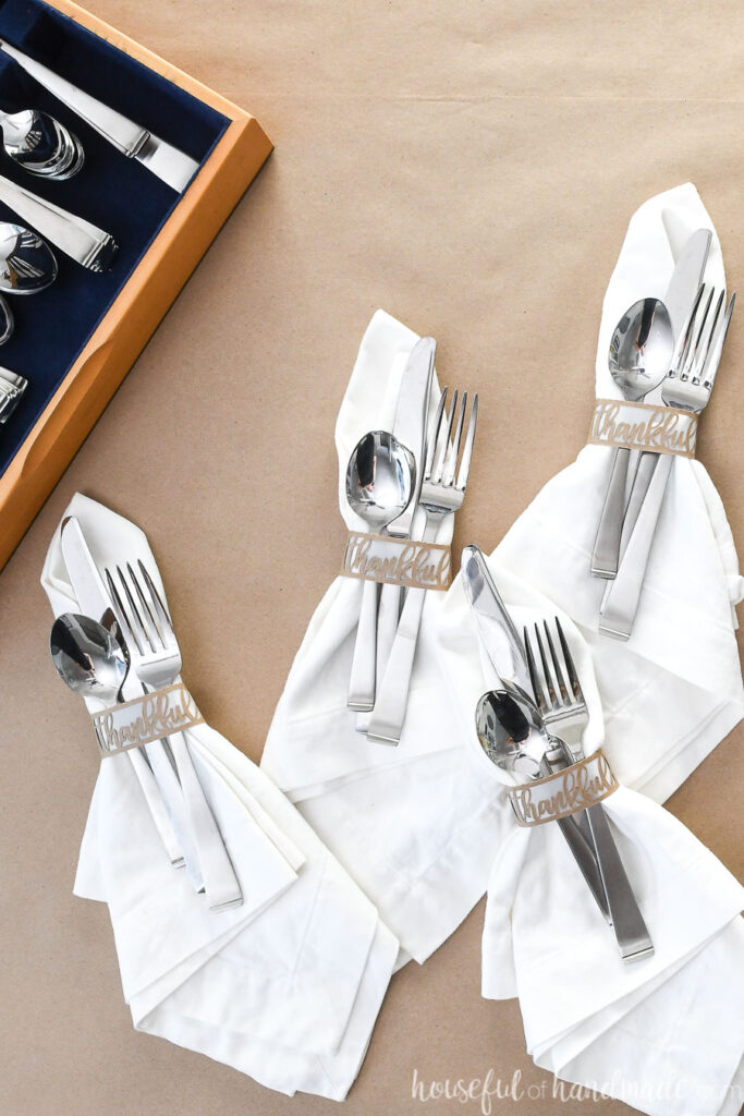 set of 4 white napkins with diy paper napkin rings and silverware