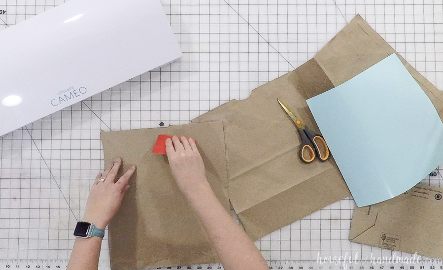 smoothing wrinkles from paper bag for diy thanksgiving napkin rings