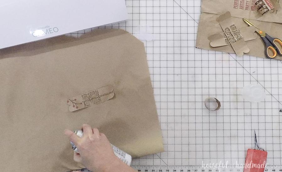 spraying adhesive glue on paper bag for diy thankful napkin rings
