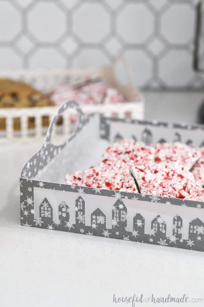 set of 2 paper christmas cookie trays filled with cookies on counter
