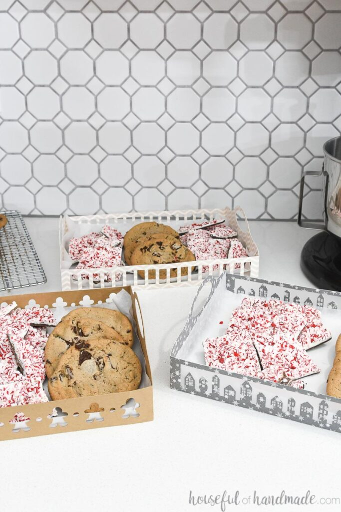 3 paper christmas cookie trays on counter with hexagon background
