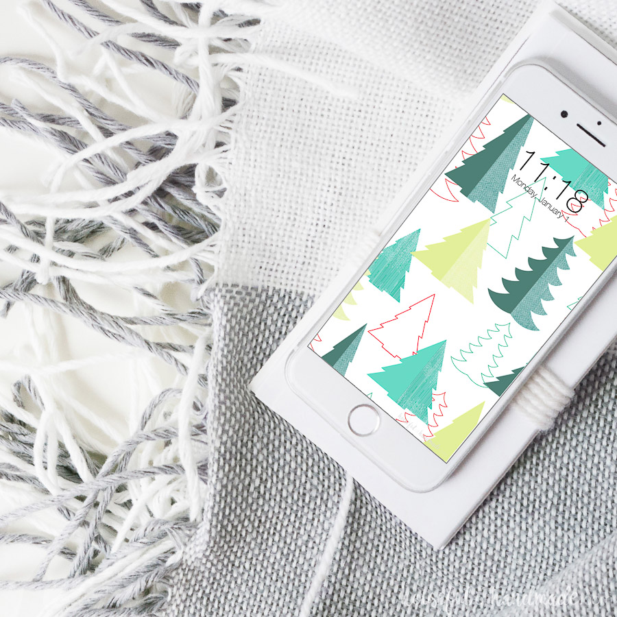White iPhone with Christmas tree pattern on the back for the free digital wallpaper.