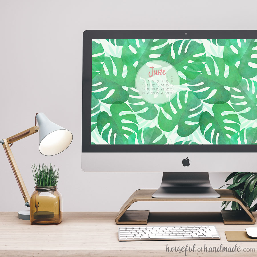 Water color palm leaf digital wall paper on an iMac computer next to a lamp and decorative jar.