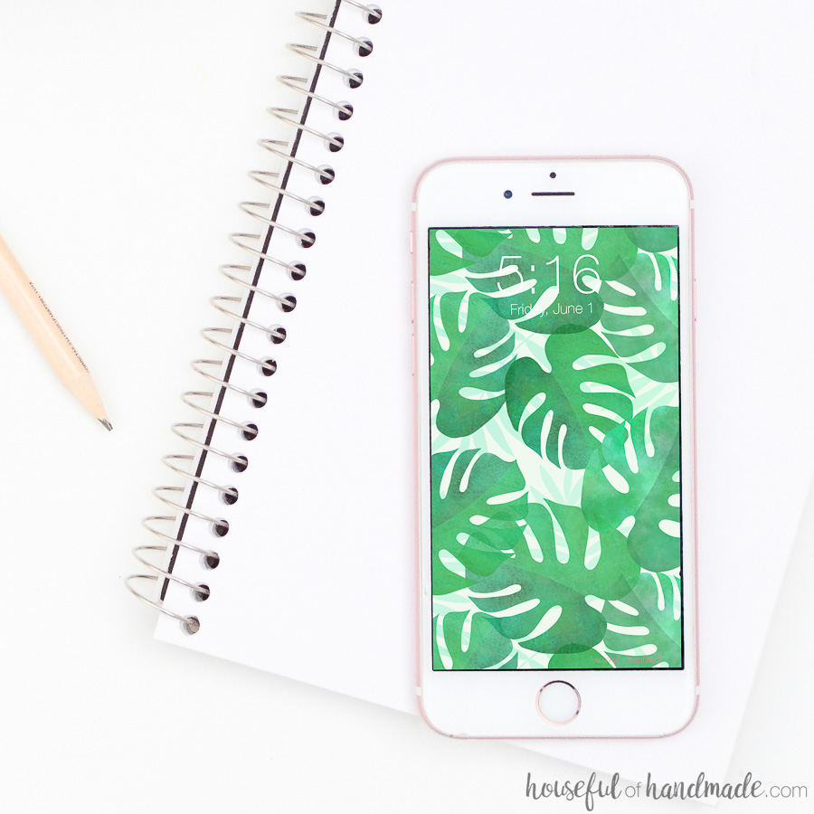 iPhone vertically placed on a white note book displaying a tropical leaf watercolor pattern.