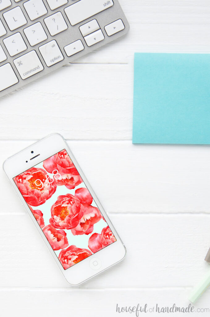 Floral phone wallpaper on a smartphone on a desk.