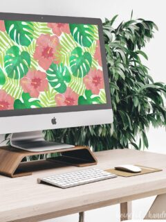 iMac on a desk with digital water color art of hibiscus. Plant in the back round and keyboard and mouse on the desk.