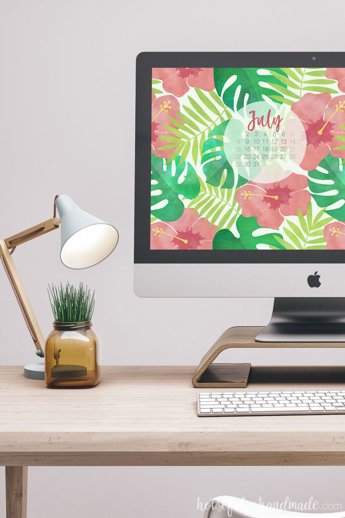 iMac on a desk with lamp displaying water color digital wall paper with a calender.